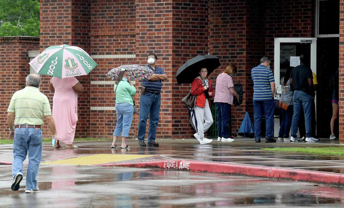 Voters make their way through showers to get in line to vote at Rogers Park on election day Saturday. Photo made Saturday, May 1, 2021 Kim Brent/The Enterprise
