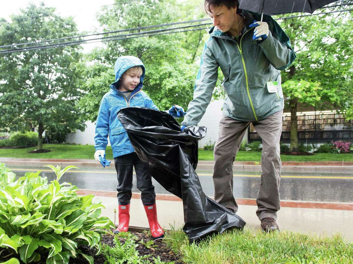 6-year-old Charlie Davidson and his father, Doug, collect trash on a rainy Saturday during Town Cleanup Day.