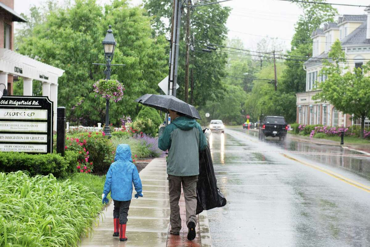 6-year-old Charlie Davidson and his father, Doug, collect trash on a rainy Saturday during