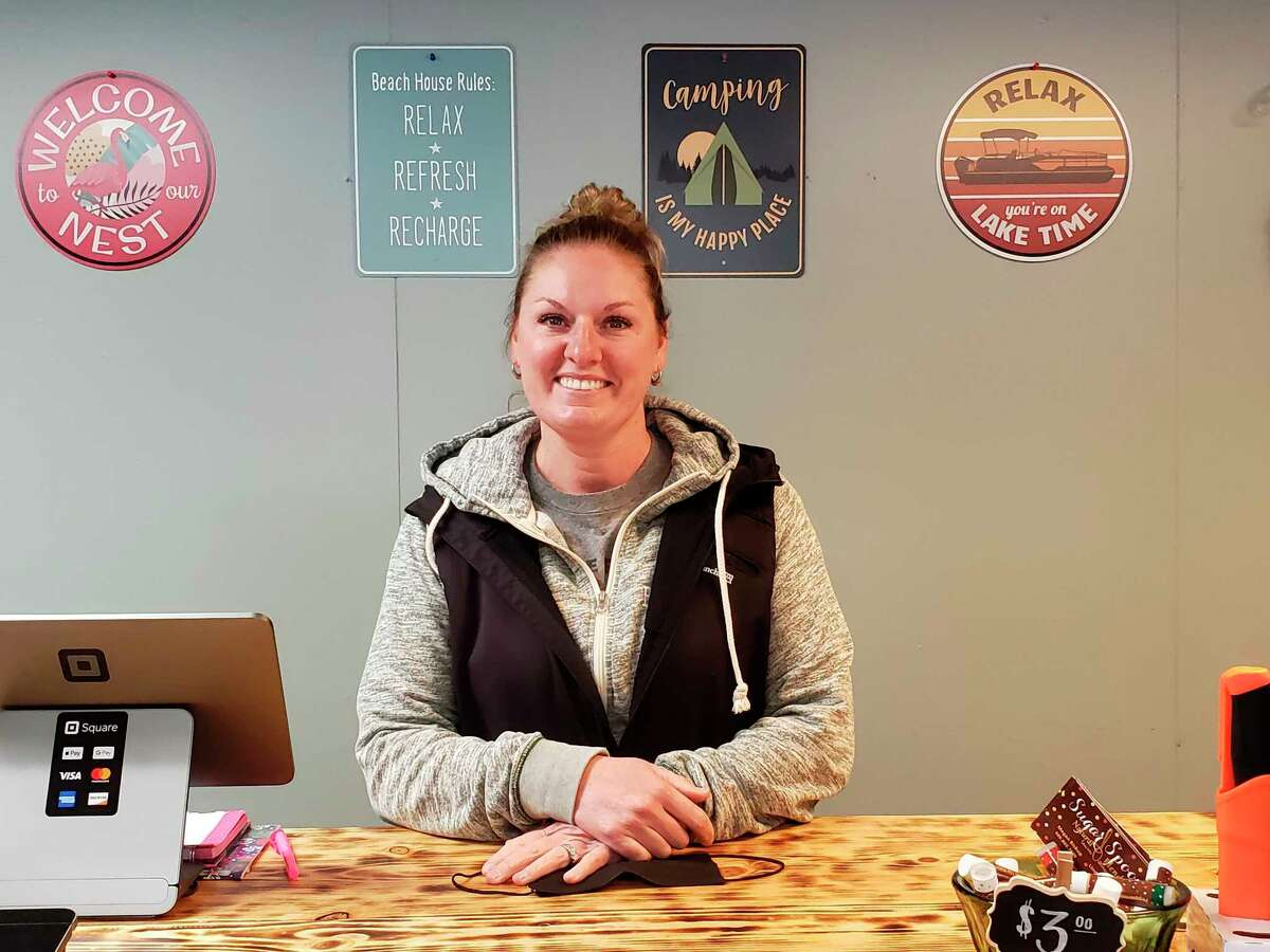 Kristen Zagorski behind the counter at Lakeland Outfitters, a new outdoor goods store in Caseville. Zagorski said this store grew out of a similar store she runs at Beadle Bay Marina. (Robert Creenan/Huron Daily Tribune)