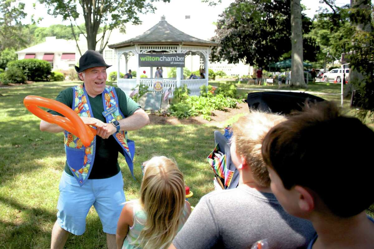 Mr. Bungles makes a balloon rattle snake for children during the fifth annual Wilton street fair, and sidewalk sales in a previous year. Mr. Bungles is also returning for the Wilton Chamber of Commerce's ninth annual events on Saturday, July 24, 2021, from 10 a.m. to 3 p.m.
