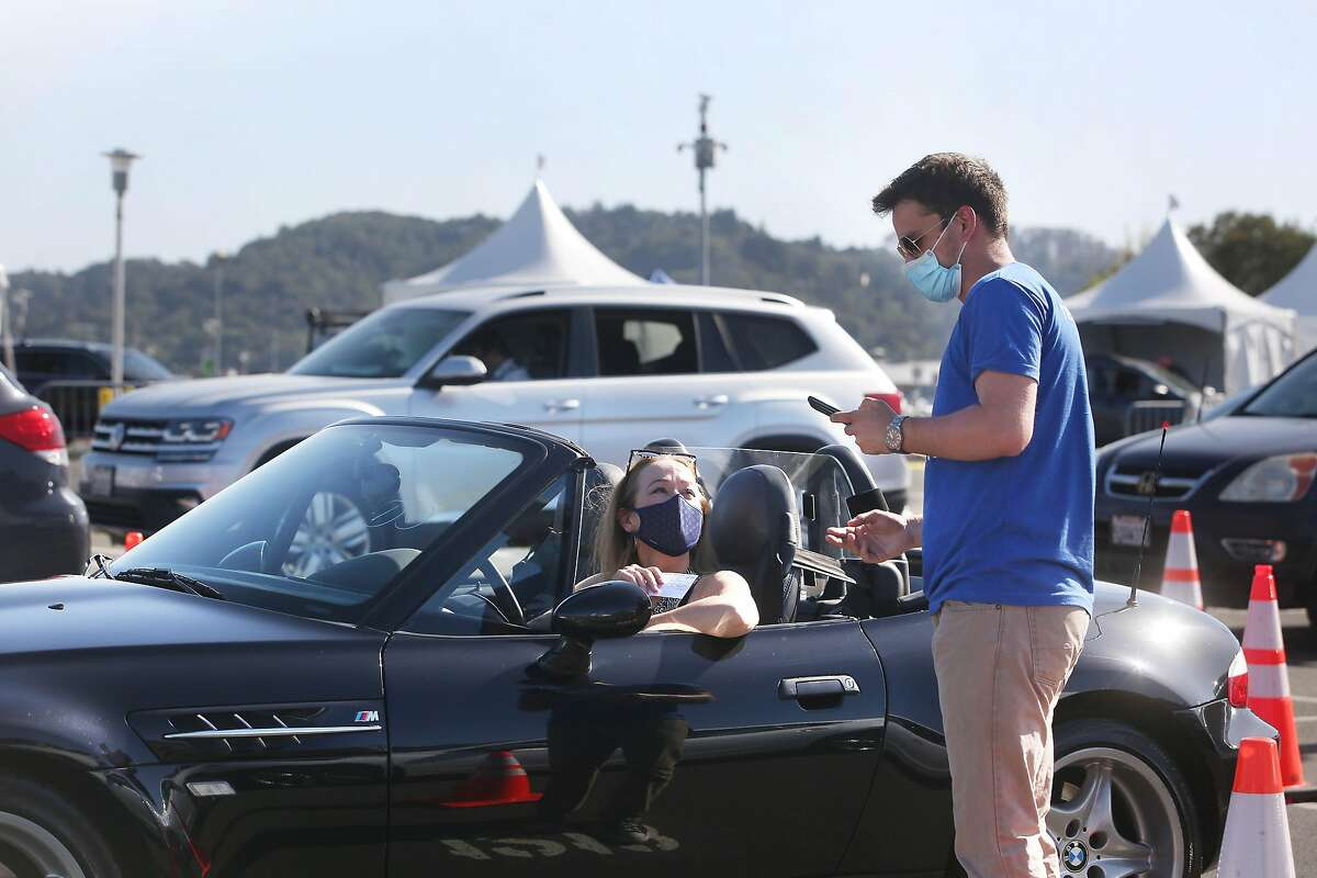 Kristina Skierka (left) of Lucas Valley makes an appointment for her second shot of COVID-19 vaccine with Jackson Murphy at the drive-through vaccination clinic at Larkspur Ferry Terminal on April 1. Marin County officials credited high vaccination rates for the county's move into the yellow tier Tuesday.