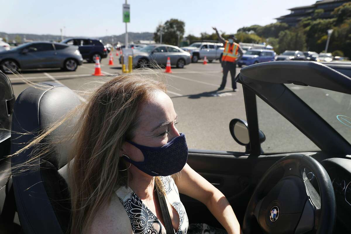 Kristina Skierka of Lucas Valley waits in a line of cars to receive her first dose of COVID-19 vaccine at the Larkspur Ferry Terminal. Marin County officials credited high vaccination rates for the county's move into the yellow tier Tuesday.