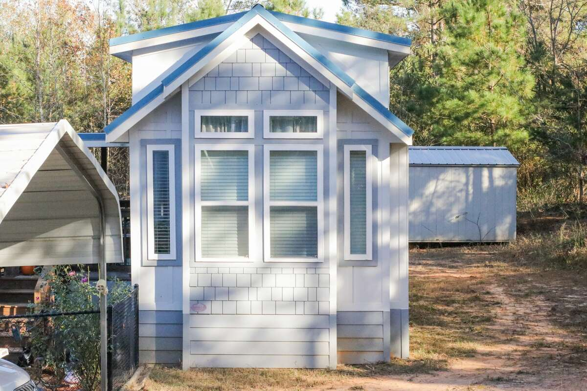 Front end of a blue tiny house with under skirting and storage unit in the back. Shaded windows in the front of tiny home. Fence