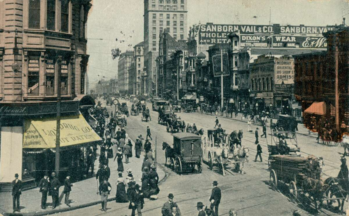 Market Street, with pedestrians in formal dress, horse-drawn carriages and storefronts, some with selective hand-coloring, and the Sanborn Vail and Company and Dixon buildings visible, San Francisco, 1911.