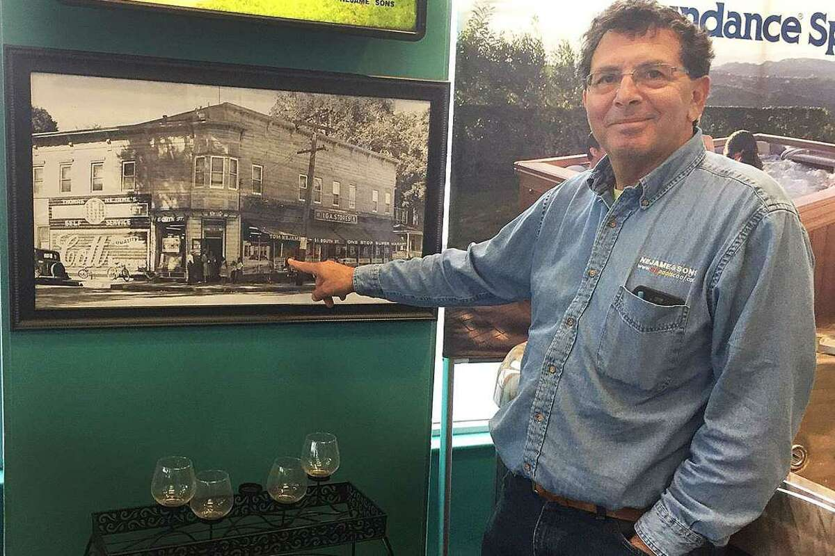 Tom Nejame, co-owner of Nejame & Sons, points to an undated photograph of the general store that opened in 1921 and was the start of the Nejame family business in Danbury, Conn. Tuesday, April 4, 2017.