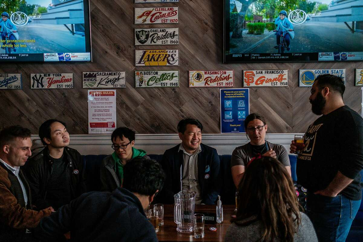"""Brian Quan, center in a blue blazer, enjoys an evening out with his friends at Trademark & Copyright sportsbar in San Francisco on Saturday, May 29, 2021. Mr. Quan completed Mayor Breed's """"small business challenge"""" for the month of May by visiting a variety of small business in alphabetical order."""