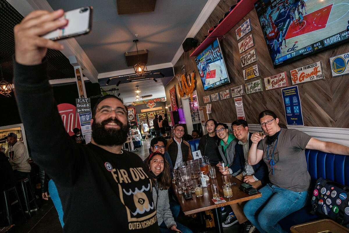 """Brian Quan, second from right, poses for a selfie while out with his friends at Trademark & Copyright sportsbar in San Francisco on Saturday, May 29, 2021. Mr. Quan completed Mayor Breed's """"small business challenge"""" for the month of May by visiting a variety of small business in alphabetical order."""