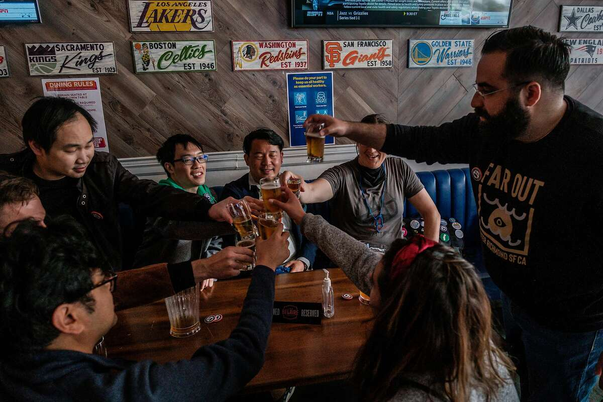 """Brian Quan, center in a blue blazer, and his friends cheers each other at Trademark & Copyright sportsbar in San Francisco on Saturday, May 29, 2021. Mr. Quan completed Mayor Breed's """"small business challenge"""" for the month of May by visiting a variety of small business in alphabetical order."""