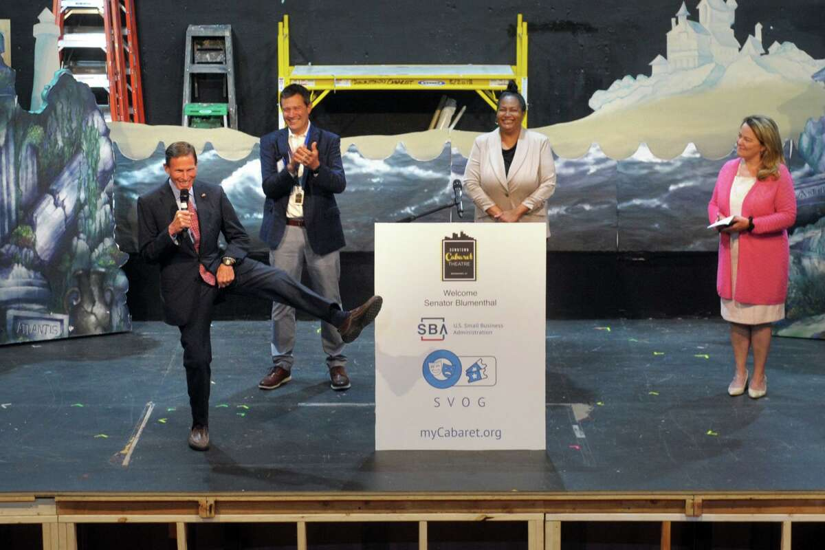 U.S. Sen. Richard Blumenthal does a dance kick while he speaks on the stage of the Downtown Cabaret Theater, in Bridgeport, Conn. June 1, 2021. Blumenthal joined others to announce the theater will receive a $541,000 Shuttered Venues Operators Grant (SVOG).
