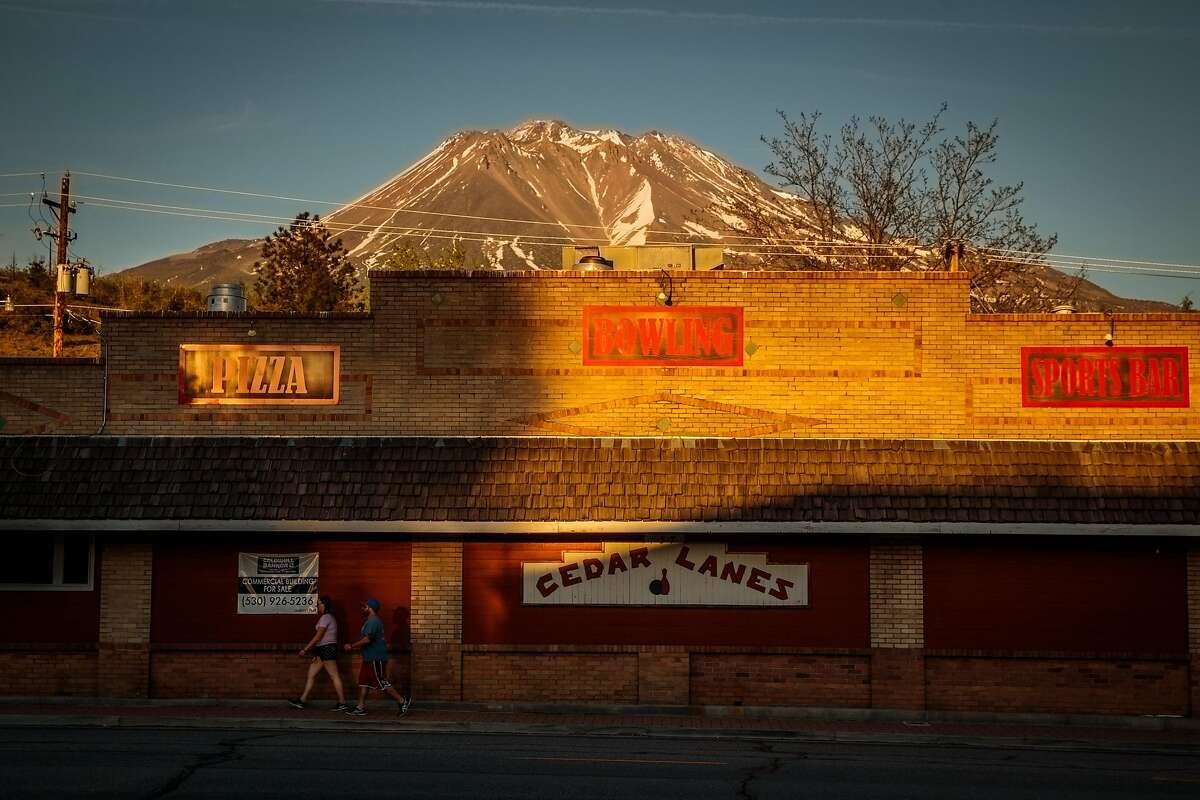 Mount Shasta looks over the shoulder of downtown Weed. The region is seeing rising coronavirus infections.