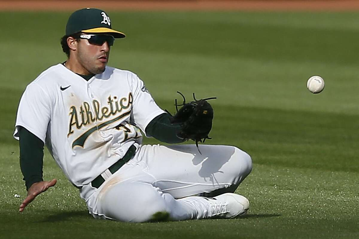 Oakland Athletics center fielder Ramon Laureano (22) misses the fly ball in the seventh inning during the first game of an MLB doubleheader against the Minnesota Twins at RingCentral Coliseum on Tuesday, April 20, 2021, in Oakland, Calif.
