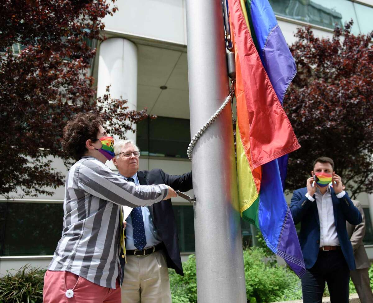 Stamford Pride secretary Selina Policar, left, and Stamford Mayor David Martin raise a rainbow LGBTQ+ pride flag outside the Government Center in Stamford on Tuesday.