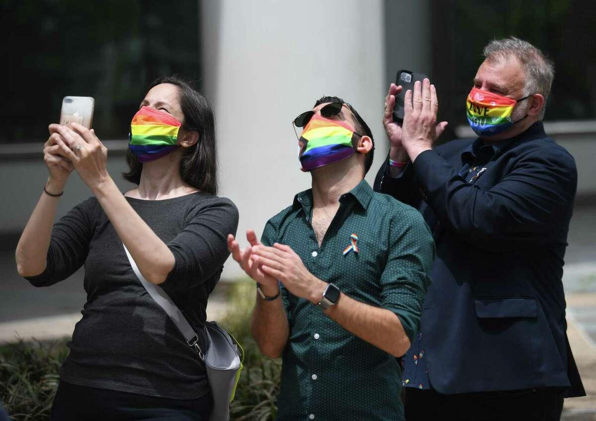 Stamford Pride board members Wendy Skratt, left, Nicolas Mendoza, center, and Chris Koutsovitis applaud as a rainbow LGBTQ+ pride flag is raised