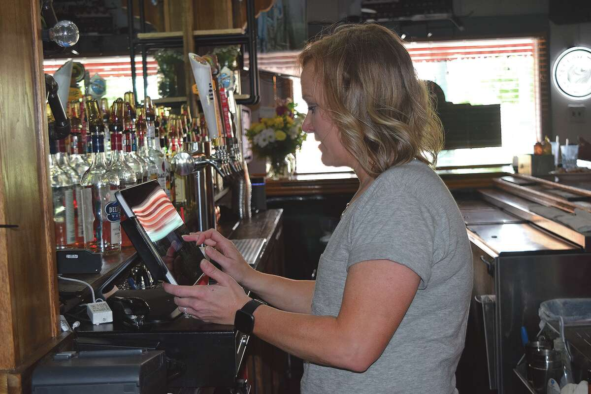 Owner Katie Guseman operates the cash register Tuesday at Guse's Pub and Eatery in Jacksonville. The restaurant opened during the holiday weekend.