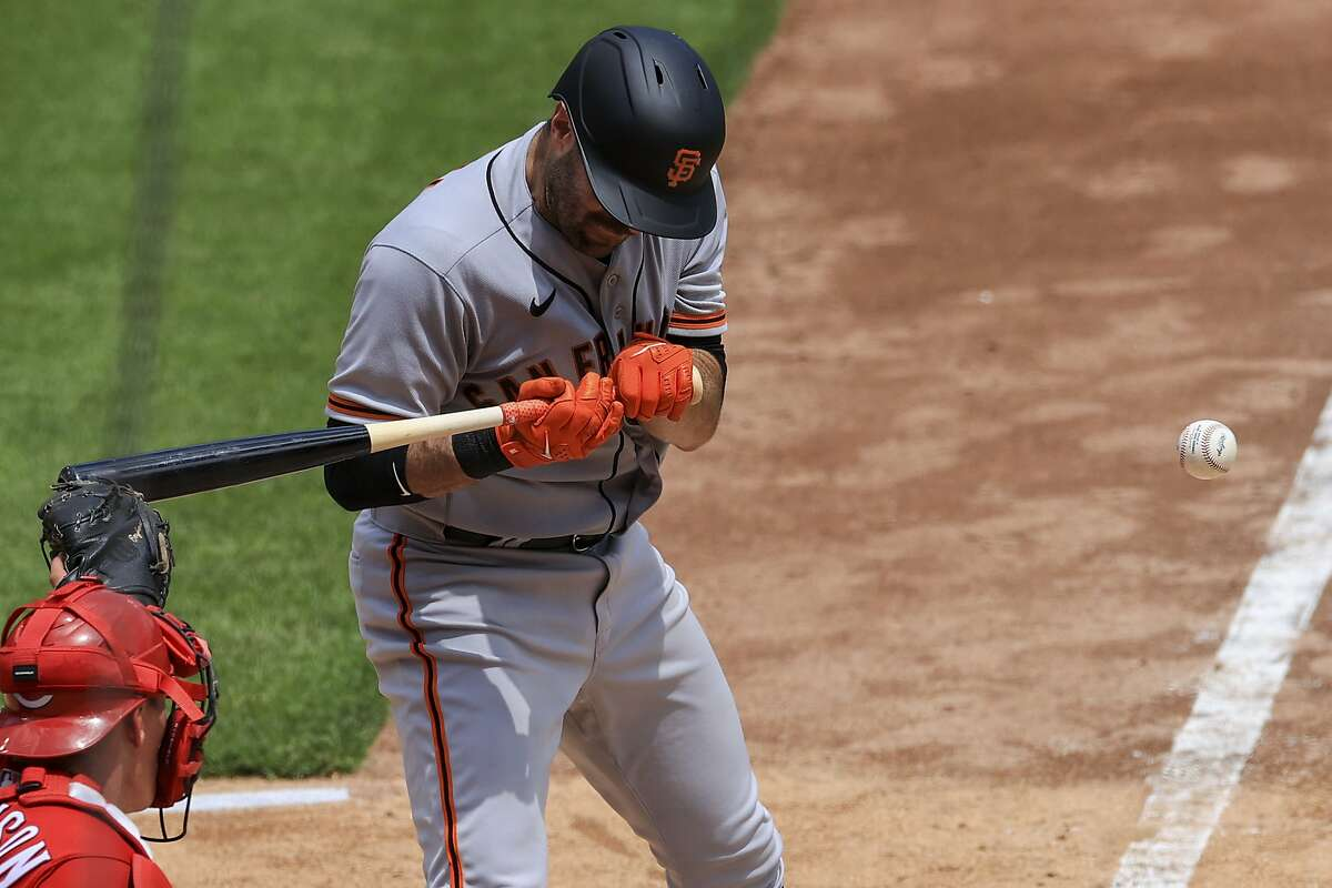 San Francisco Giants' Curt Casali reacts after being hit by a pitch during the fifth inning of a baseball game against the Cincinnati Reds in Cincinnati, Thursday, May 20, 2021. (AP Photo/Aaron Doster)