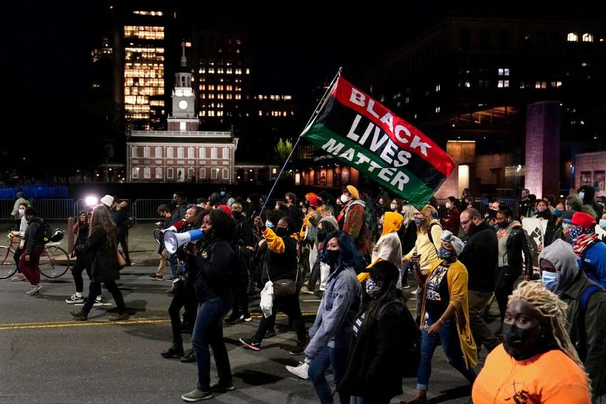 Demonstrators march past Independence Hall to urge that all votes be counted in Philadelphia following the November election.