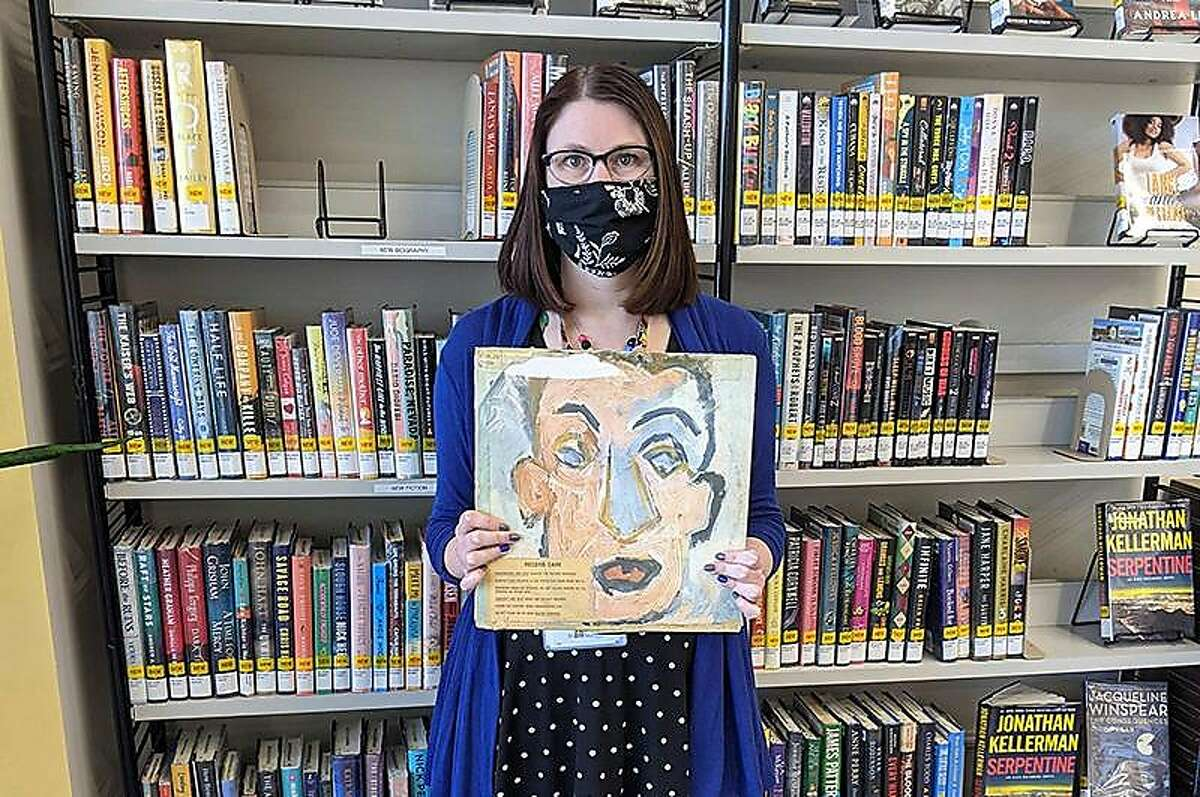 """Heights Libraries Branch Manager Sara Philips holds Bob Dylan's """"Self Portrait"""" that San Francisco resident Howard Simon returned recently 48 years overdue."""