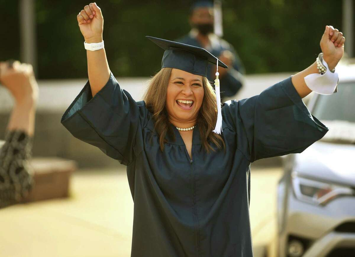 Graduate Jackeline Borges celebrates as she walks up to receive her diploma at the Bridgeport Adult Education Graduation at Central High School in Bridgeport, Conn. on Tuesday, June 1, 2021.