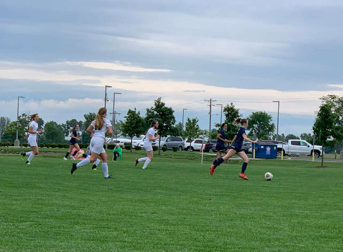 Father McGivney's Mary Harkins fires a shot on goal during Tuesday's game against Metro-East Lutheran. Harkins scored a program-record four goals in the team's first playoff win.