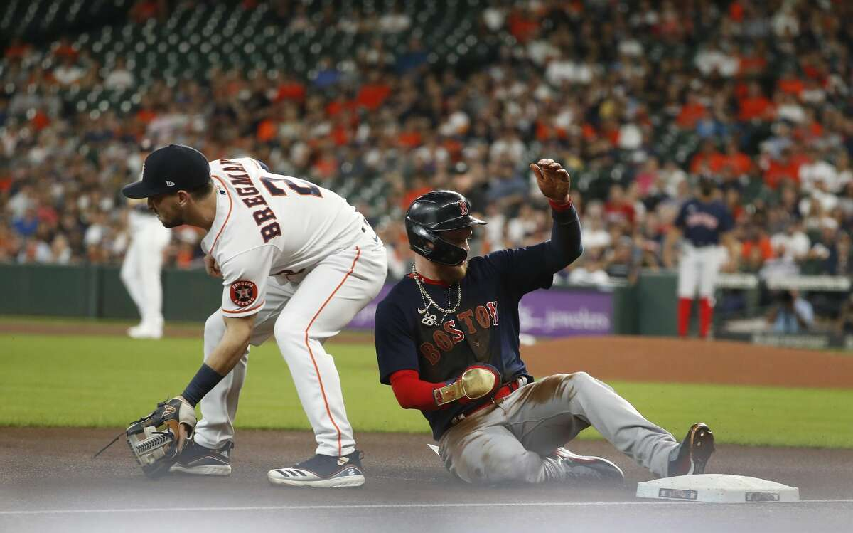 Boston Red Sox Alex Verdugo (99) slides into third base after stealing second base and advanced to third on a throwing error by Houston Astros catcher Martin Maldonado during the first inning of an MLB baseball game at Minute Maid Park, Tuesday, June 1, 2021, in Houston.
