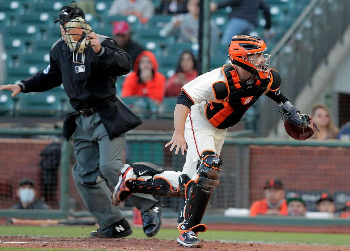 Buster Posey (28) scrambles after a wild pitch by Alex Wood (57) that scored Andrew Heaney (28) in the third inning as the San Francisco Giants played the Los Angeles Angels at Oracle Park in San Francisco, Calif., on Tuesday, June 1, 2021.