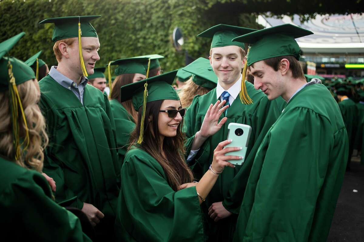 From left, Alex Rich, Marissa Zajac, Matt Wright and Dean Zorn video chat with a friend as the H. H. Dow High School Class of 2021 celebrate with a commencement ceremony Friday at Dow Diamond in Midland. (Katy Kildee/kkildee@mdn.net)