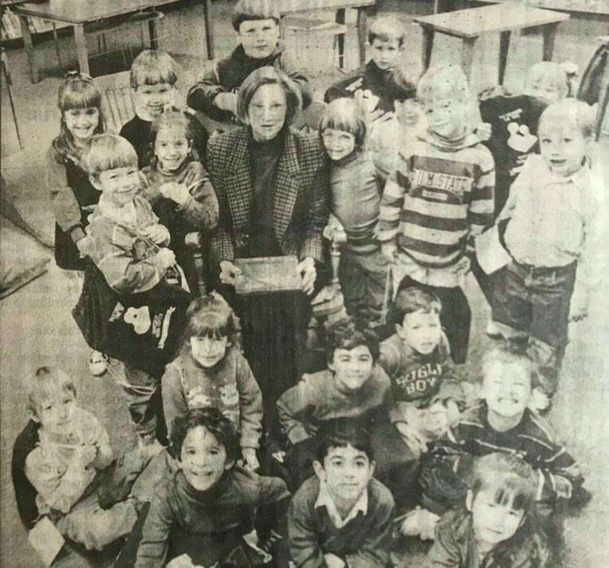 Pat McCallum is surrounded by Woodcrest Elementary School kindergarten students and their Togetherness Totes in the Woodcrest library. December 1993