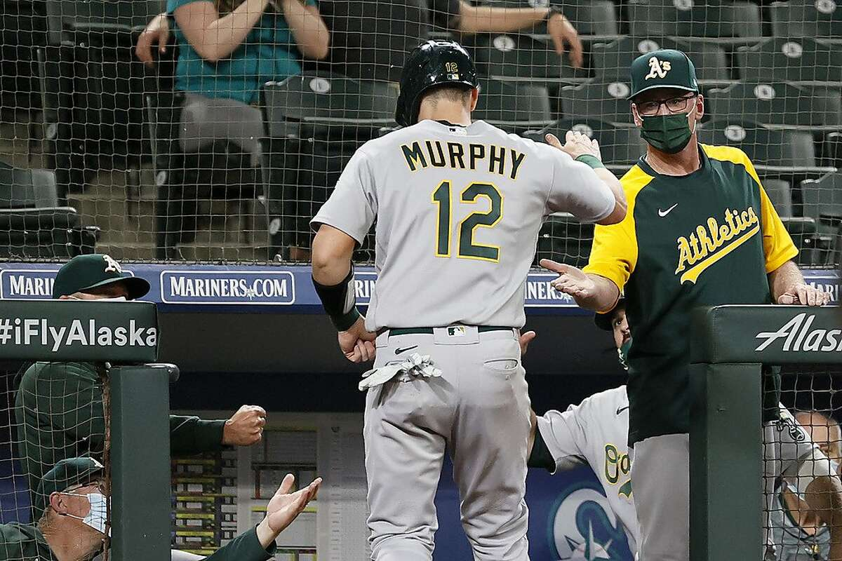 SEATTLE, WASHINGTON - JUNE 01: Manager Bob Melvin of the Oakland Athletics high fives Sean Murphy #12 after a run against the Seattle Mariners during the ninth inning at T-Mobile Park on June 01, 2021 in Seattle, Washington. (Photo by Steph Chambers/Getty Images)