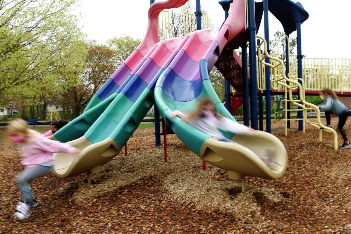 Children play on the playground during recess at Springdale Elementary School in Stamford, Conn. Thursday, April 29, 2021.