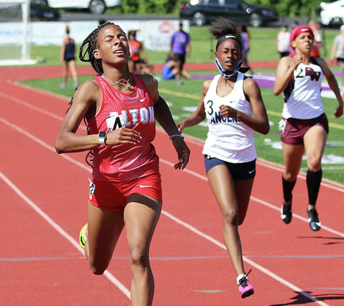 Alton's Renee Raglin (left) crosses the finish line in the 200 to complete her 100 and 200 title sweep in the SWC Meet last week at Collinsville.
