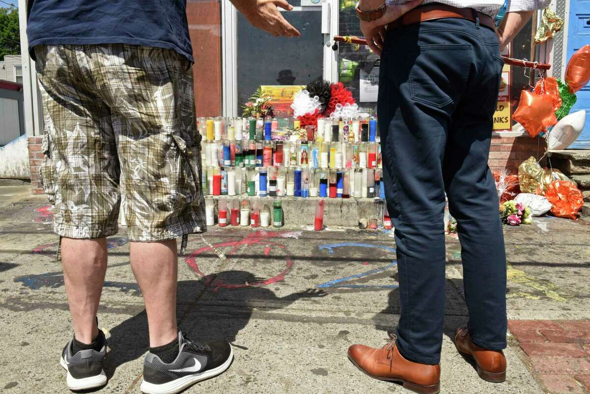 Michael Greene, left, and Greg Aidala talk while looking at a memorial at the scene of Friday's deadly shooting at First and Quail outside Mr. Sam Food Market on Monday, May 24, 2021 in Albany N.Y. The memorial was put in place to honor longtime store worker, Sharf Addalim, know to locals as David, who was killed after being caught in a drive-by shooting. Aidala, who's family owns an auto sales business next door and Greene, who lives close to the store, were both at the scene and felt helpless as they witnessed the life leave the body of Addalim. (Lori Van Buren/Times Union)