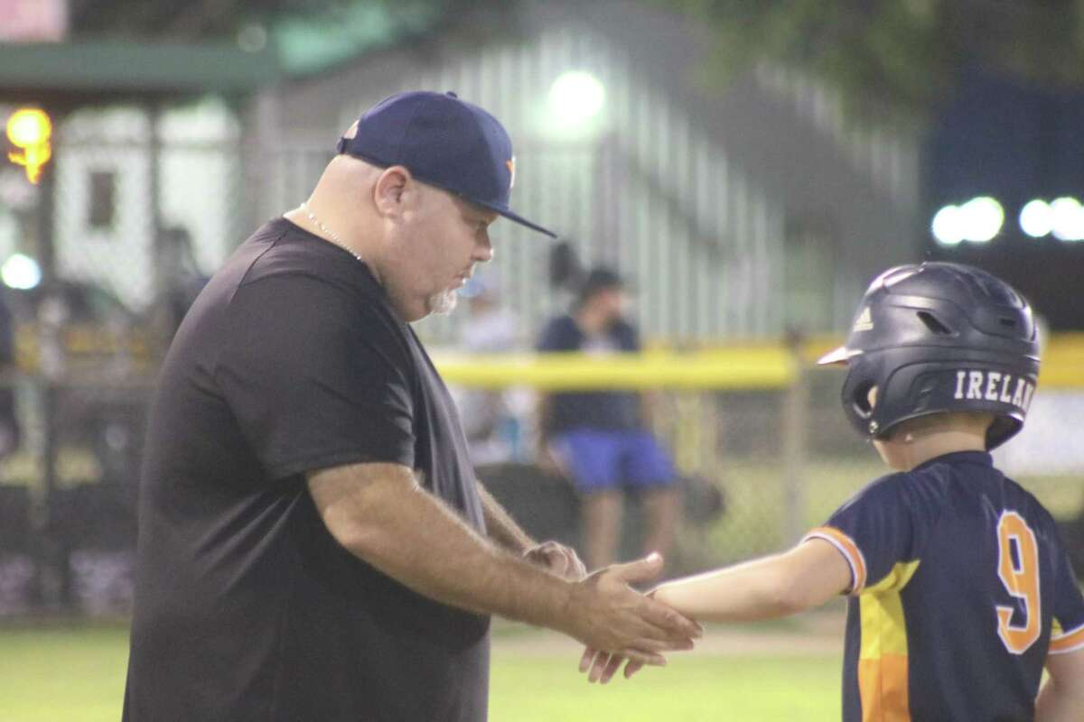 Astros coach Chris Bornscheuer works the sting out of Aiden Ireland's hand after he was hit with a pitch during Tuesday night's Majors Division tournament game at Joseph Fleming Field.