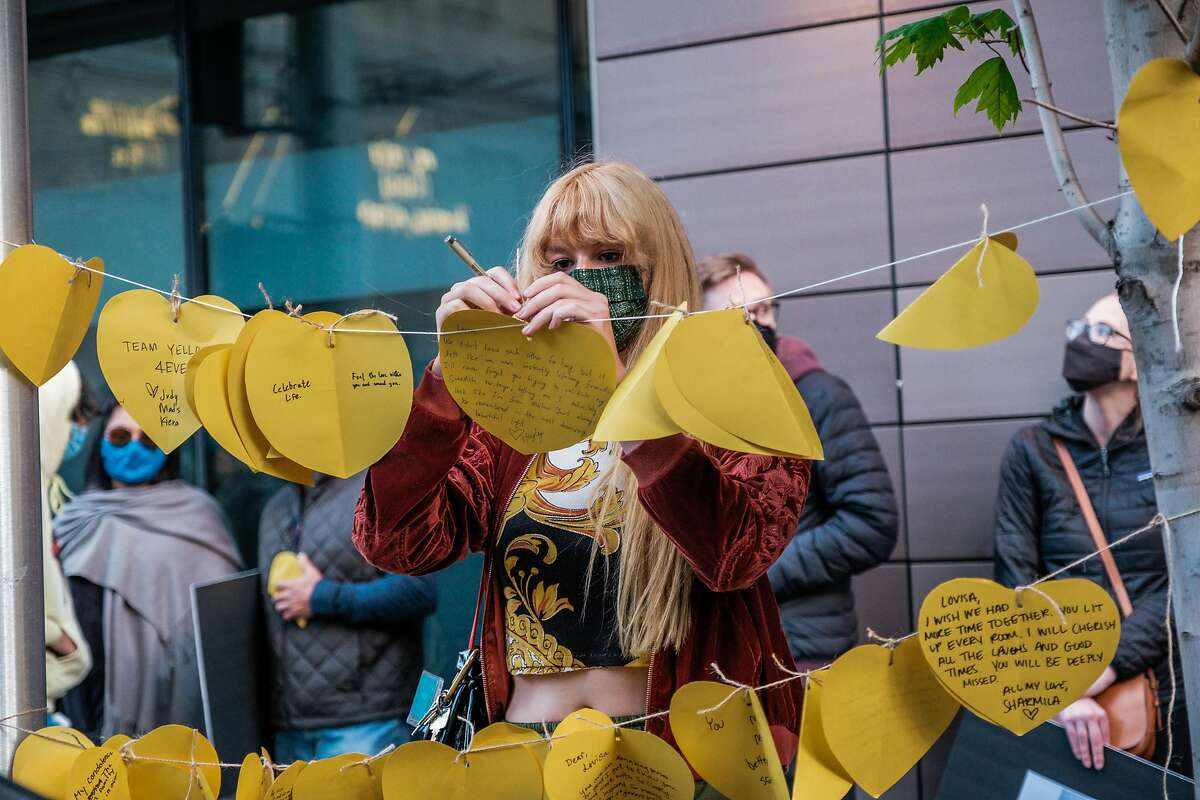 Hayley Becon hangs a note on the corner of Polk and Hayes during a vigil honoring Lovisa Svallingson who was killed in a hit and run accident that also critically injured her boyfriend Danny Ramos in San Francisco on Wednesday, May 27, 2021.