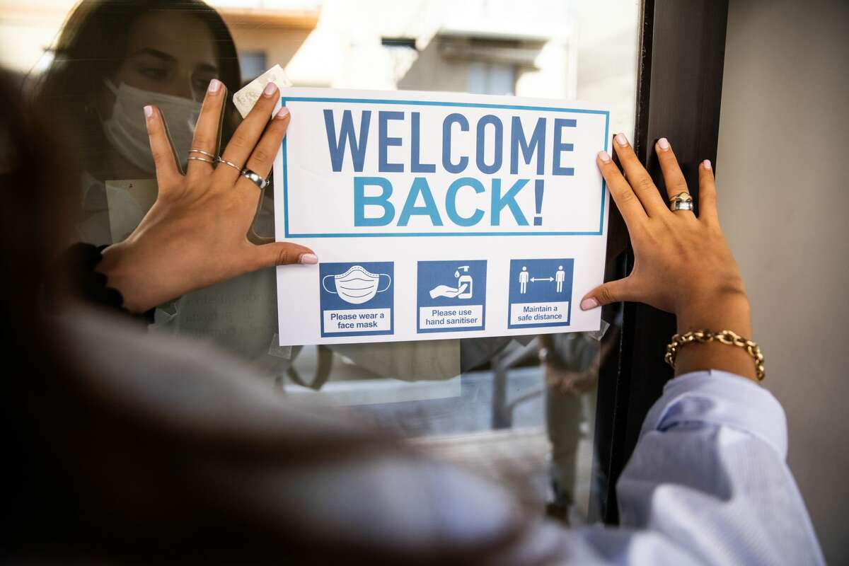"""Woman applying """"Welcome Back"""" sign after COVID-19 pandemic."""