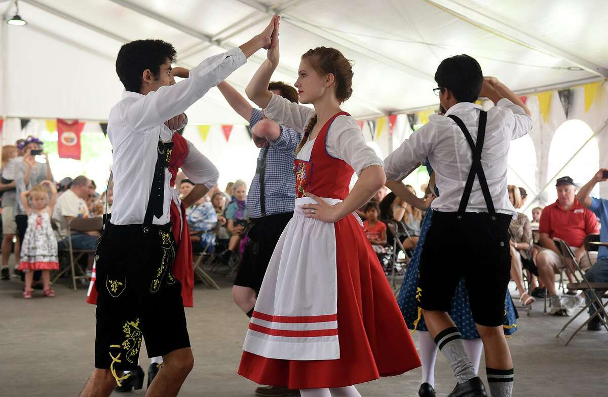 Katy Tompkins High School juniors Sarah Rogers, 17, center, and Joshua Lake, 17, left, perform as part of the school's German Club folk dancing group during the Tomball German Heritage Festival in downtown Tomball on April 1, 2017. (Photo by Jerry Baker/Freelance)