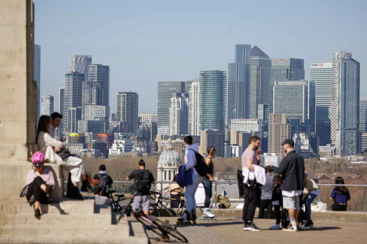 People relax in Greenwich Park in view of the Canary Wharf business, shopping and financial district in London.