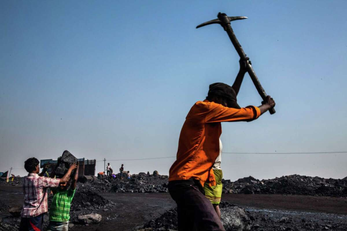 A day laborer breaks coal using a pick at an open pit coal mine in the Bestacolla Colliery in Jharia, Jharkhand, India, on April 6, 2014.