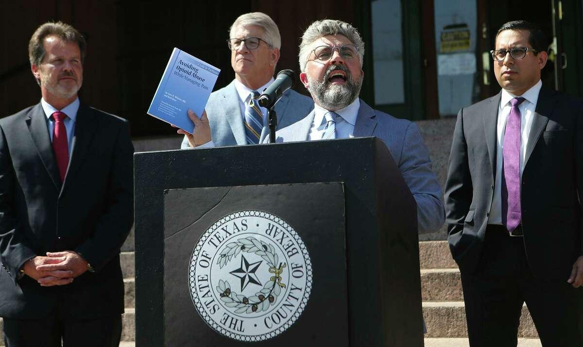 Attorney Martin Phipps (at lectern) announces in 2018 that Bexar County has filed suit against opioid manufacturers, promoters, and distributors. Facing a telephone harassment charge, Phipps is asking that a special prosecutor replace the Bexar County District Attorneys Office in the case, arguing that its involvement in the lawsuit is a conflict of interest.