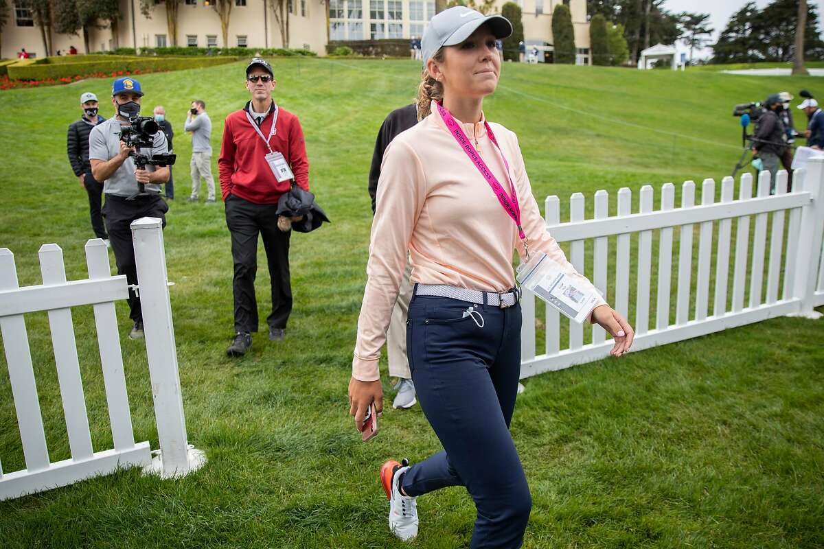 Rachel Heck walks to a media tent to be interviewed before her practice round for the U.S. Women's Open at the Olympic Club, Wednesday, June 2, 2021, in San Francisco, Calif. Her father, Robert Heck (in red), is her caddie.