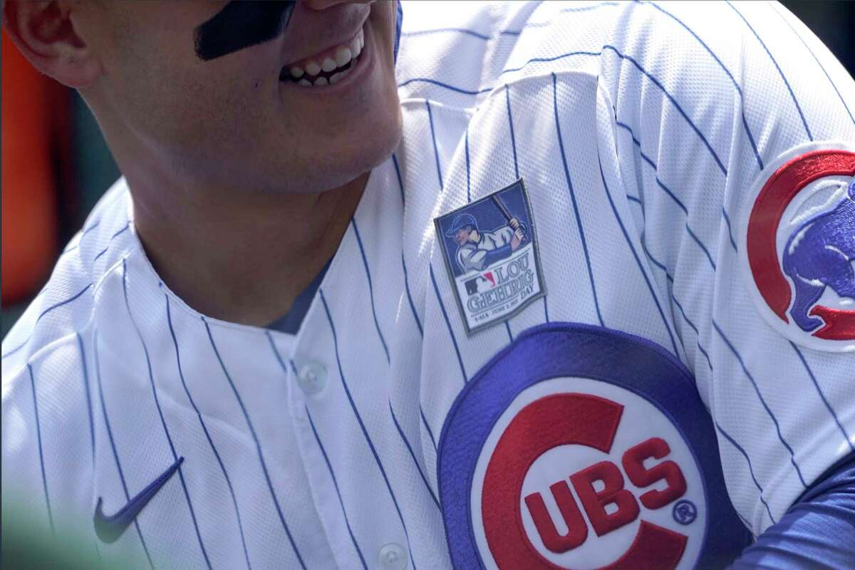 In an image shot through COVID-19 protective plexiglass, Chicago Cubs first baseman Anthony Rizzo smiles in the dugout wearing a Lou Gehrig patch before a baseball game against the San Diego Padres Wednesday, June 2, 2021, in Chicago. (AP Photo/Charles Rex Arbogast)