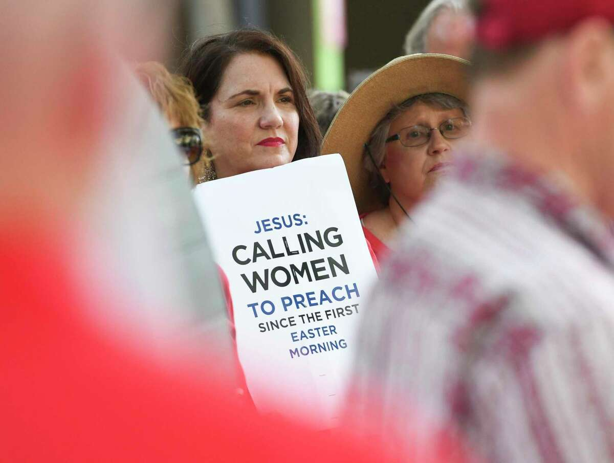 FILE - In this Tuesday, June 11, 2019 file photo, Janene Cates Putman of Athens, Tenn., holds a sign during a demonstration outside the Southern Baptist Convention's annual meeting in Birmingham, Ala. Among the millions of women belonging to churches of the Southern Baptist Convention, there are many who have questioned the faith's gender-role doctrine and more recently urged a stronger response to disclosures of sexual abuse perpetrated by SBC clergy. (AP Photo/Julie Bennett)