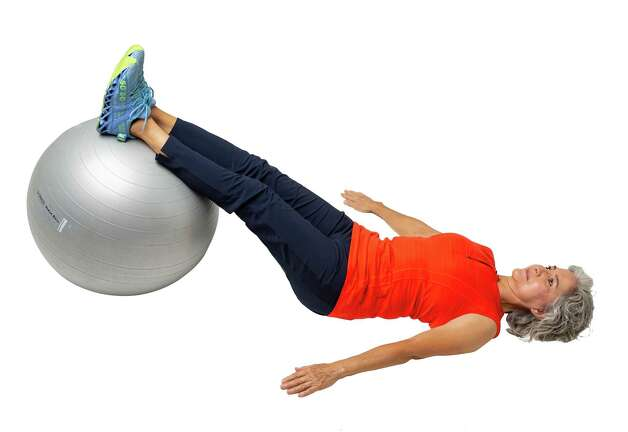 Lie face up with your calves and feet on top of stability ball. Press into the ball and lift your hips off the floor. Photo: Godofredo A. Vásquez, Houston Chronicle / Staff Photographer / © 2021 Houston Chronicle