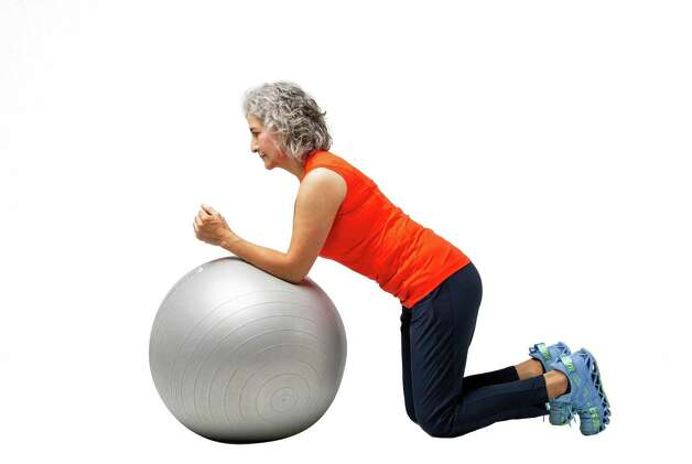 Kneel in front of the stability ball with your elbows on the ball. Tighten your quads and straighten your legs. Photo: Godofredo A. Vásquez, Houston Chronicle / Staff Photographer / © 2021 Houston Chronicle