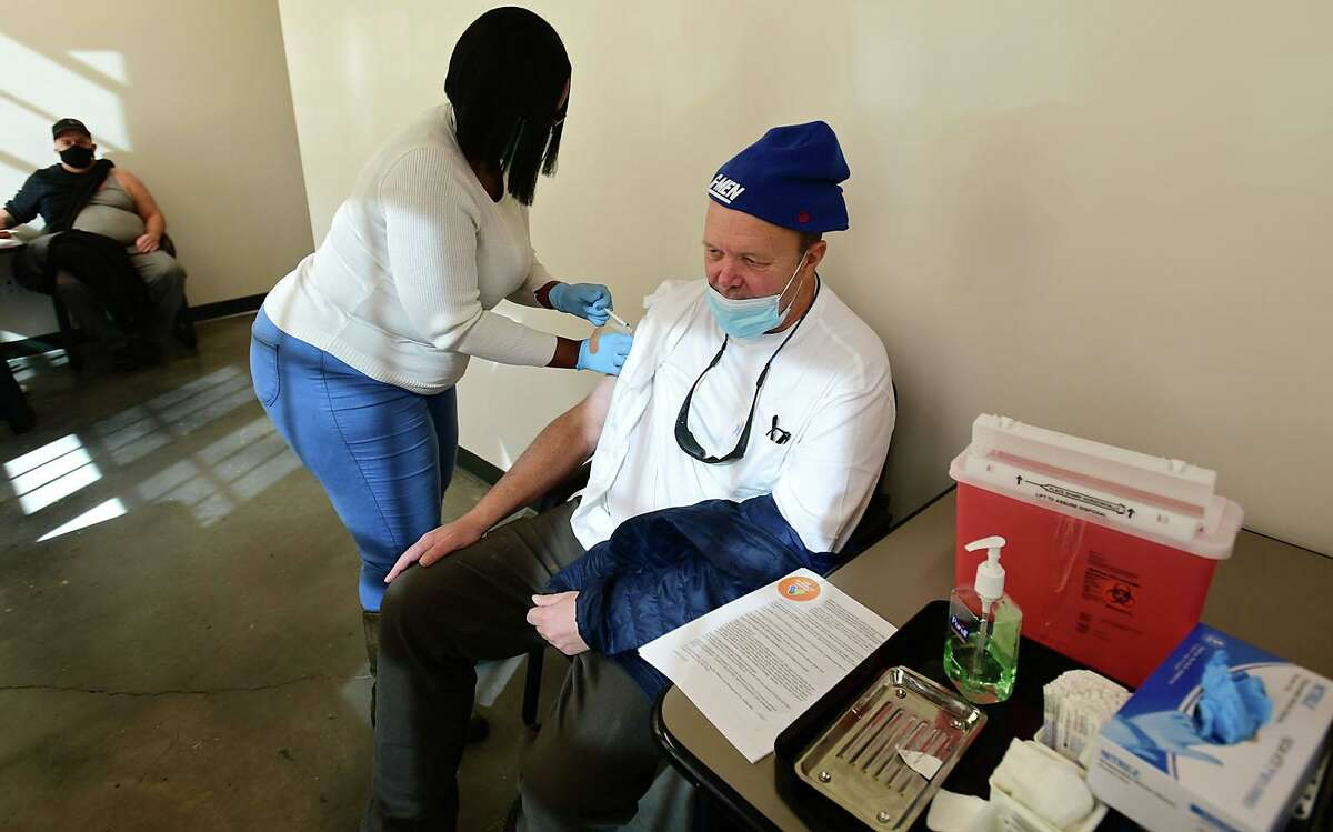 Open Door homeless shelter client Ted Bancroft receivs the injeection as the shelter administers its first corona virud vaccines for residents and staff by Norwalk Community Healthcare Center nurse Yolanda Taylor Friday, February 12, 2021, at the Smiloe Lice Center in Norwalk, Conn.