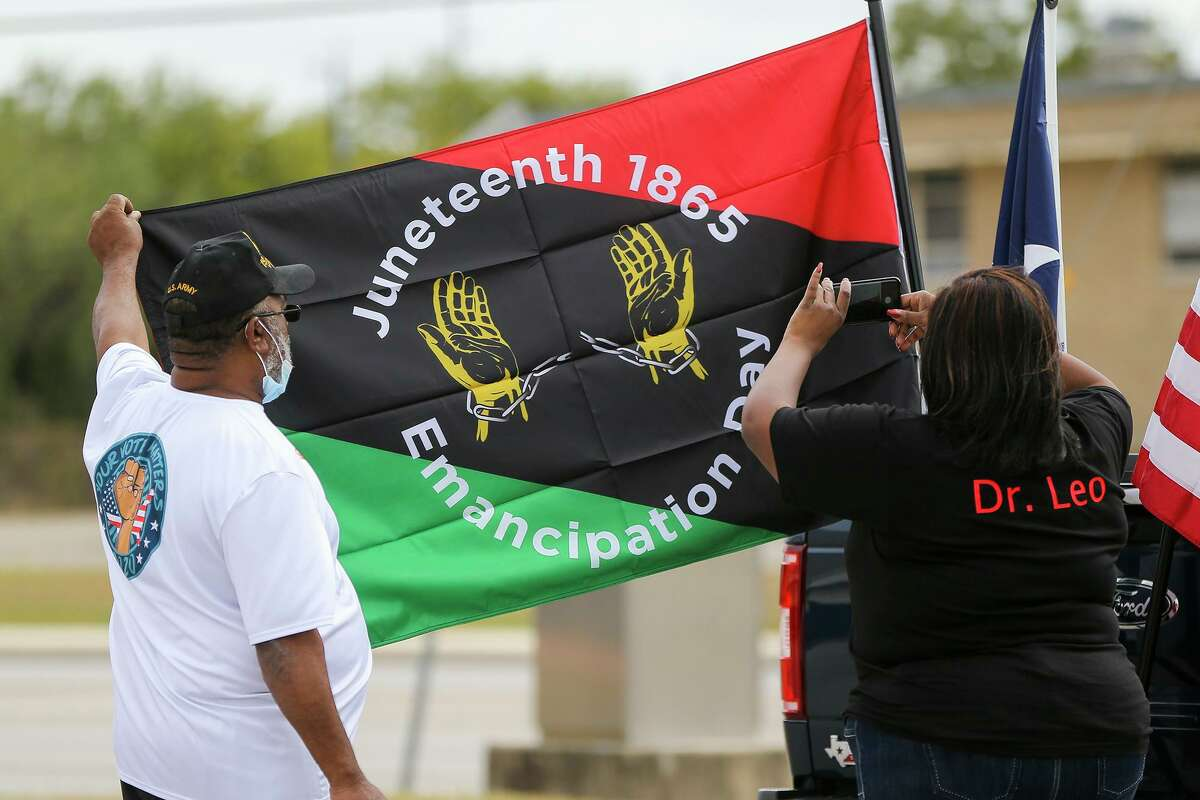 """Leonetta Green takes a photo of a Juneteenth 1865 Emancipation Day flag held by Sam Mills as participants assemble for the """"Souls to the Polls"""" voter turnout drive at Sam Houston High School on Sunday, Oct. 25, 2020, before heading in a caravan to the Claude Black Community Center on East Commerce Street to cast their votes. There are several free and ticketed events to celebrate Juneteenth in San Antonio this year."""