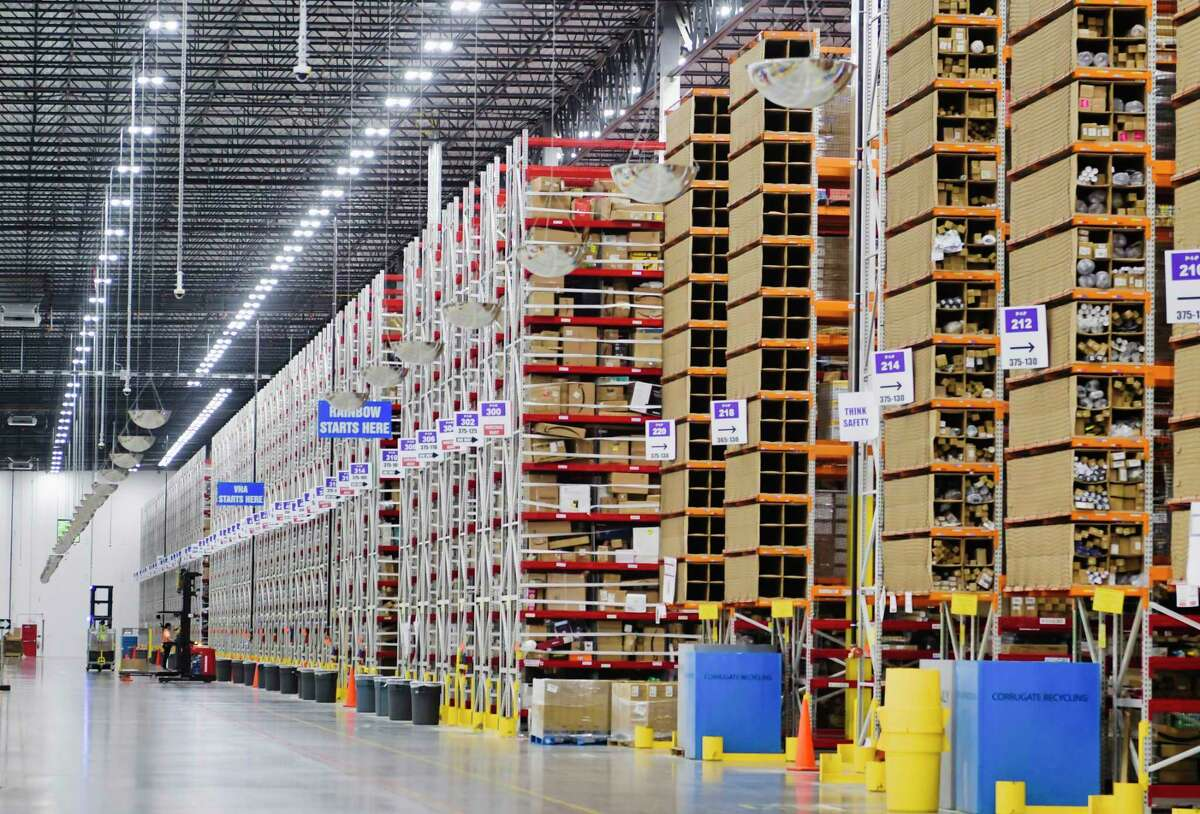 Employees move around in powered industrial trucks (PIT machines) either stocking product on shelves or pulling product for an order at the Amazon fulfillment center on Wednesday, June 2, 2021, in Schodack, N.Y. From the fulfillment center packages are sent to an Amazon sortation center or a delivery station. (Paul Buckowski/Times Union)