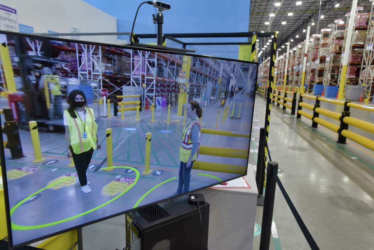 Jenna Hilzenrath, left, Amazon spokesperson, and karen Coombs, the general manager at the Amazon fulfillment center, demonstrate the distance assistant near the main entrance on Wednesday, June 2, 2021, in Schodack, N.Y. The distance assistant is an augmented reality system that provides real-time social distancing feed back to employees. Green circles means that the employees are correctly distanced. The circles turn red if employees get to close to each other. (Paul Buckowski/Times Union)