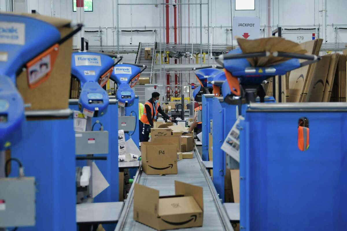 Employees box up items for customers at an Amazon fulfillment center.