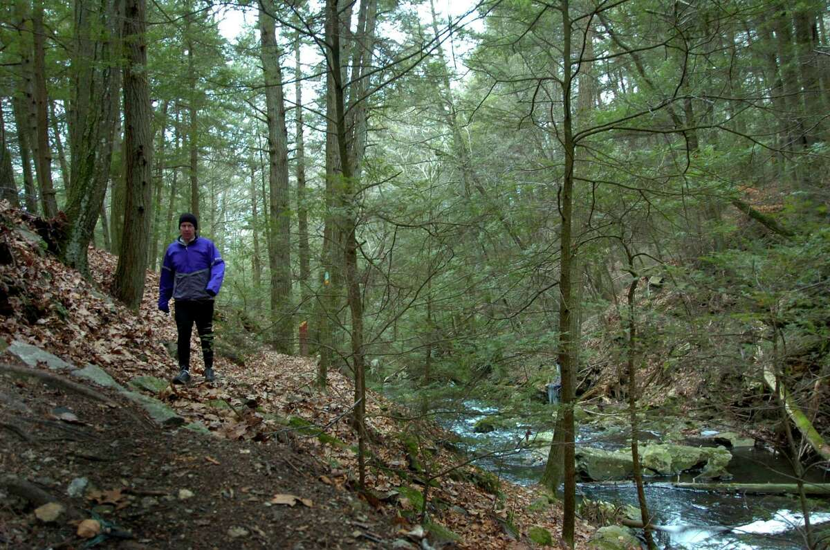 A man walks a hiking trail in the Kettletown State Park in Southbury, Conn.